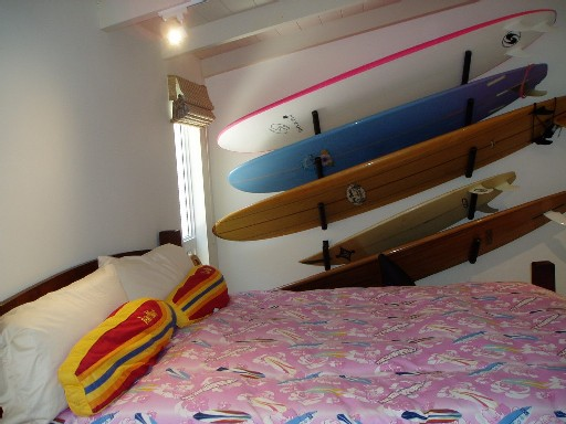 Bedroom 1 - King size bed in room decorated with various surf boards